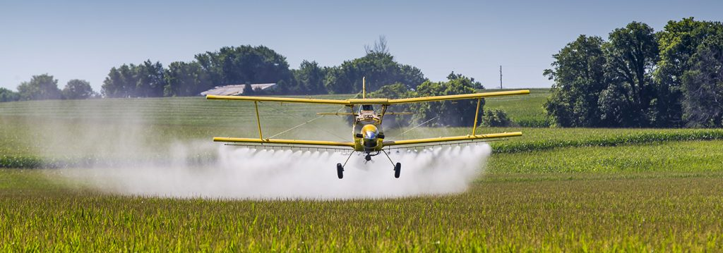 crop duster spraying field with organic chemicals